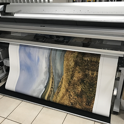 A landscape photo being printed on canvas