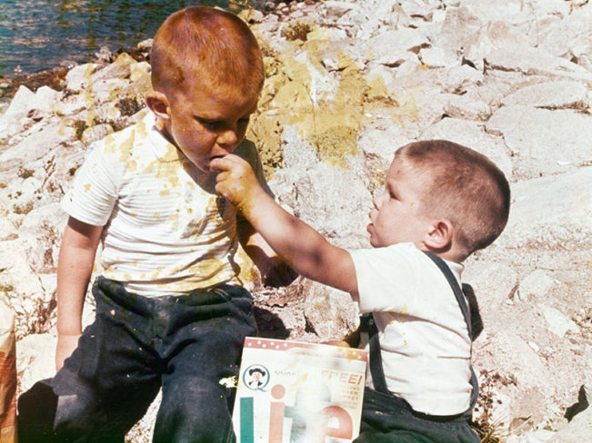 Old photo of two young boys eating cereal outside
