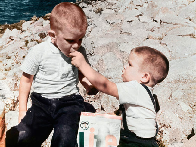 Restored photo of two young boys eating cereal outside