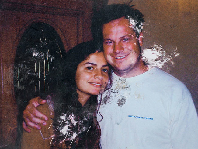 damaged photo of a young couple smiling and hugging