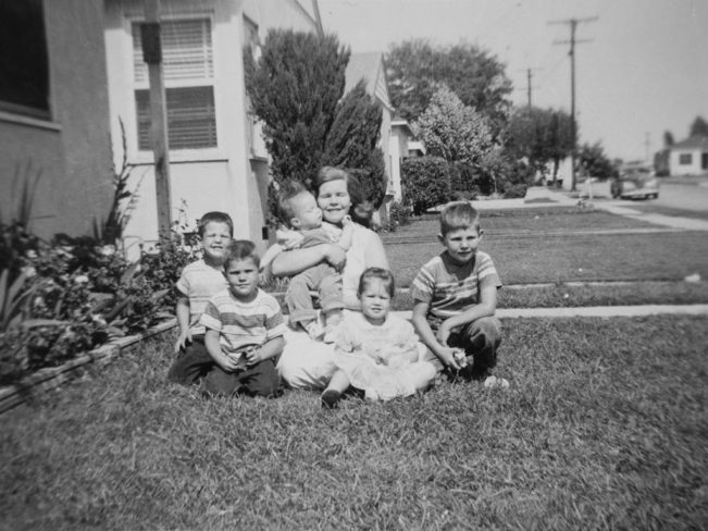 old black and white family photo in front of their house, all sitting on the grass
