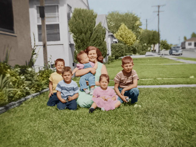 Restored family photo in front of their house, all sitting on the grass
