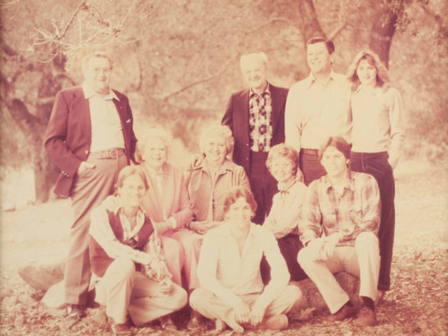 old faded yellow photo of a family smiling outdoors